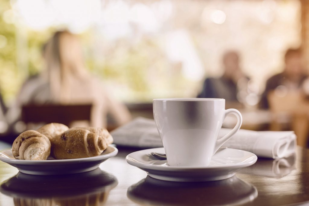 Cup of coffee on table with croissant
