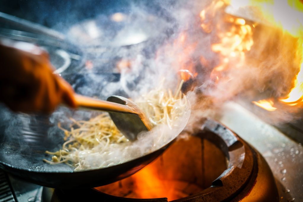 Chef in restaurant kitchen cooking Asian food